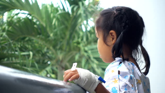 Sick childhood standing alone in hospital veranda. Real time shot in treatment. Concept of unhappy in sickness. video