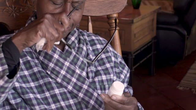 Sick elderly black woman putting on glasses to read a pill bottle
