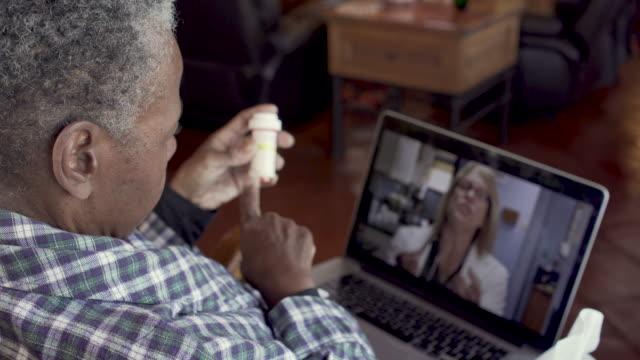 anziana donna nera malata che parla con la sua medico donna dei suoi farmaci - prescrizione medica video stock e b–roll