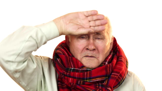 Sick grandpa wearing a scarf touching forehead having fever video