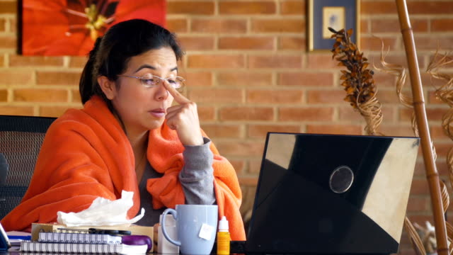 Sick Hispanic young woman working at home office. Dolly move with slow panning. video