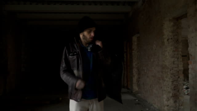 Sick homeless with garbage bag walks in abandoned building in search of food video