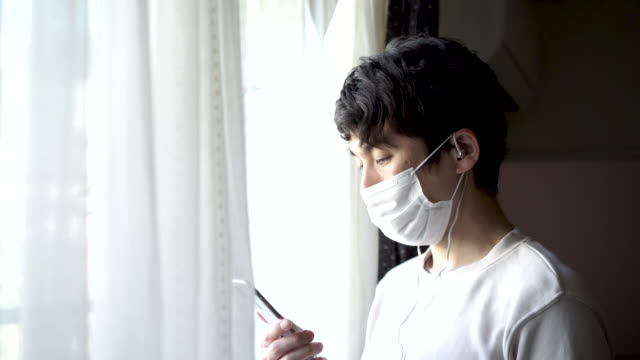 A sick Japanese man wearing a surgical mask is standing by the window.