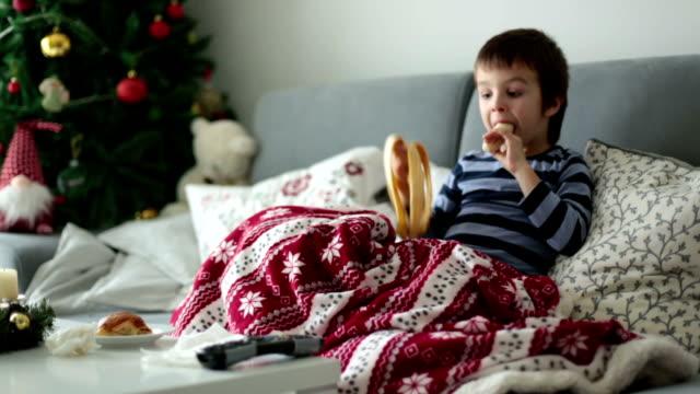 病気の小さな子供、少年、ソファの上に横たわっている間クリスマスに、クロワッサンとバナナを食べる ビデオ