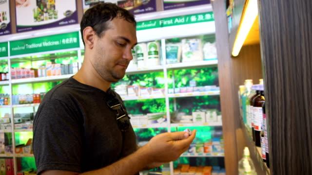 Sick Man Choosing Medicine in Pharmacy video