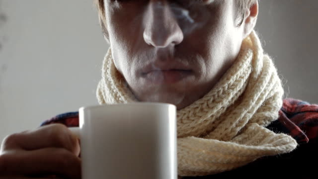sick man coughing and drinking hot tea close up of Sick young man coughing emphysema stock videos & royalty-free footage