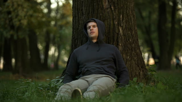 vídeos de stock e filmes b-roll de sick man feeling dizziness and faintness under tree, needs help, suffer diabetes - coração fraco