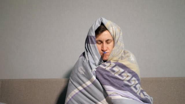 sick man in blanket taking temperature - abiti pesanti video stock e b–roll