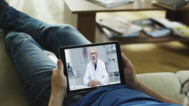 Video Sick Man Lying on a Couch and Having Video Conversation with His Doctor on a Tablet Computer.