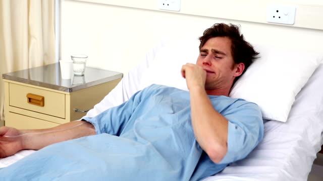 vidéos et rushes de homme malade allongé sur le lit d'hôpital tousser - allongé sur le dos