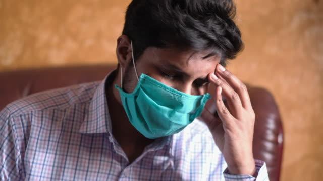 en sjuk man med en mask i ansiktet lider huvudvärk - face mask bildbanksvideor och videomaterial från bakom kulisserna