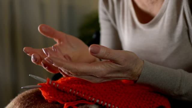 Sick old woman looking at shaking hands, unable to knit, old age difficulties Sick old woman looking at shaking hands, unable to knit, old age difficulties shivering stock videos & royalty-free footage