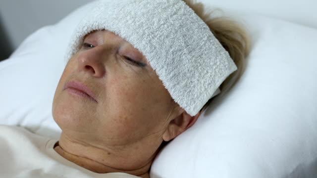 vídeos y material grabado en eventos de stock de anciana enferma con toalla en la frente acostada en la cama, sufriendo de resfriado o gripe - geriatría