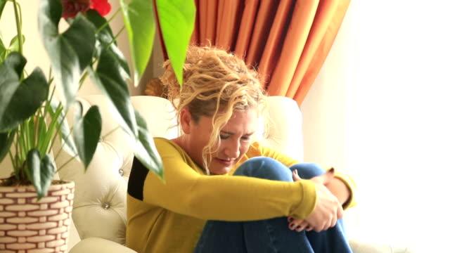 Krank, schmerzhafte Frau sitzend auf einem sofa und mit Bauchschmerzen – Video