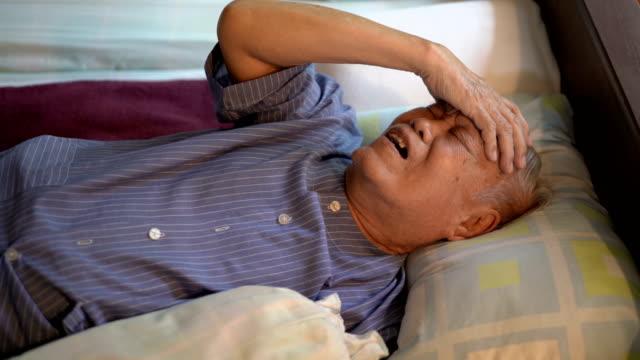 4k sick senior asian man feeling headache on bed at home - состаривание стоковые видео и кадры b-roll