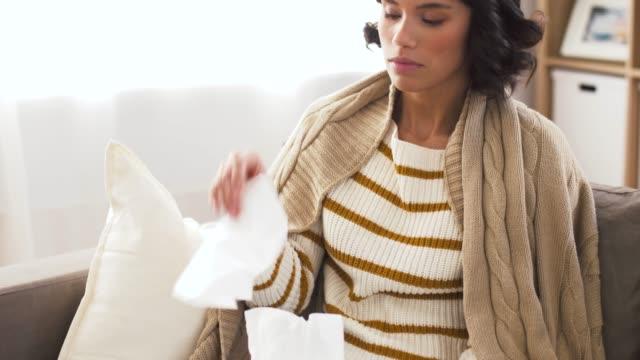 sjuk kvinna blåser näsa i pappers vävnad hemma video