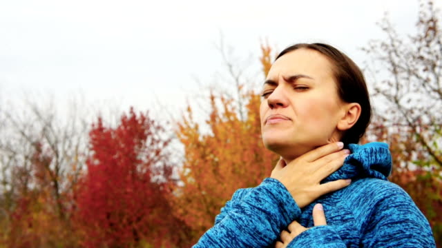 Sick woman coughing, outdoors Sick woman coughing in autumn park coughing stock videos & royalty-free footage