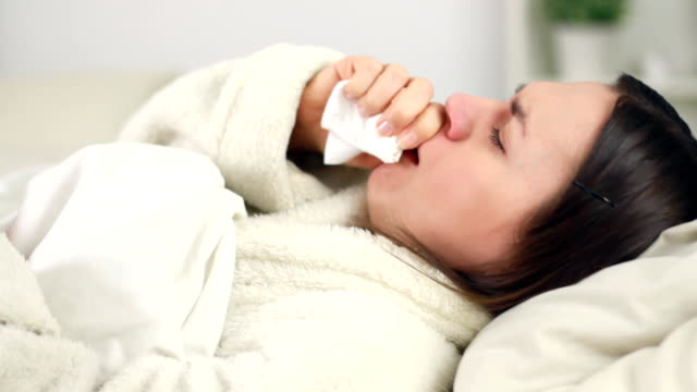 Sick woman in bed coughing and blowing nose video