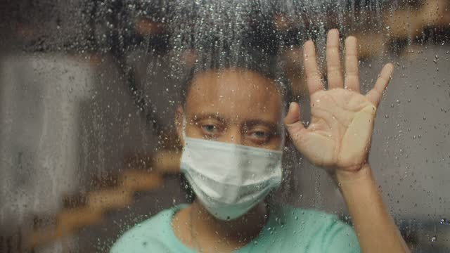 donna malata con maschera facciale che guarda fuori dalla finestra di casa - hand on glass covid video stock e b–roll