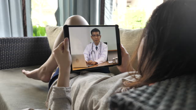 sick woman lying on a couch and having video conversation with her doctor on a tablet pc - medical exams stock videos and b-roll footage