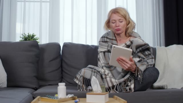 sick woman using telemedicine service on tablet - telemedicine stock videos & royalty-free footage