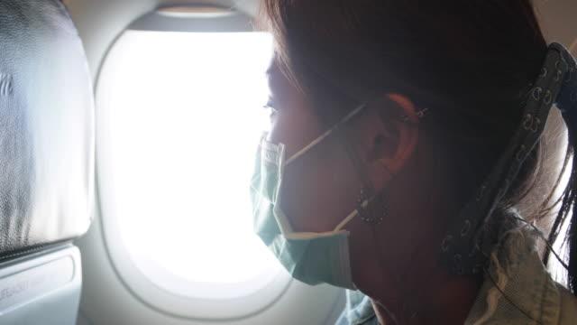 Sick woman wear face mask sit on passenger economy seat near cabin window in airplane , underexposed scene. Passenger in departure flight plane at the airport. Novel coronavirus