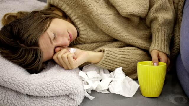 vídeos y material grabado en eventos de stock de mujer enferma con infecciones estacionales, gripe, alergia, tumbado en la cama. - flu