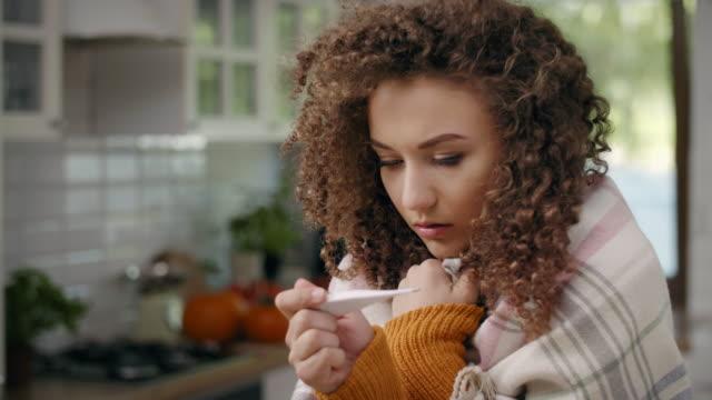 vídeos de stock e filmes b-roll de sick woman with thermometer checking temperature - doença