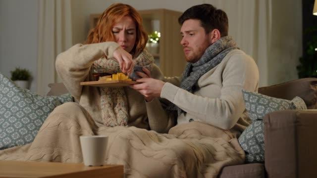 больная молодая пара пьет чай с лимоном дома - шарф стоковые видео и кадры b-roll