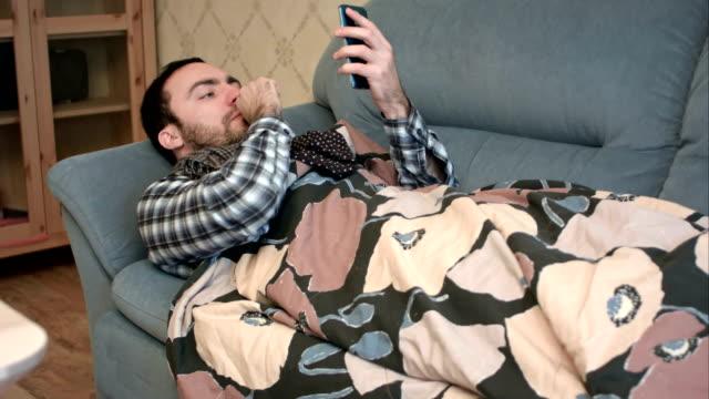 Zieke jongeman die liggen op Bank met zijn telefoon video