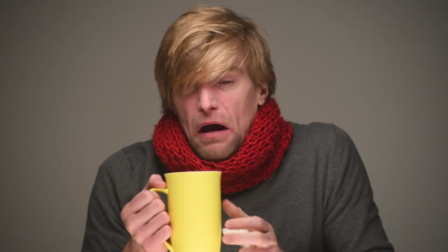 sick young man sneezes video