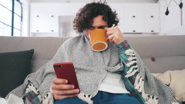vídeos de stock e filmes b-roll de sick young man using smart phone at home. - doença