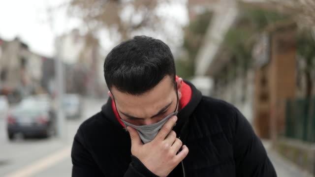 sjuk ung man bär ansiktsmask och hostar utomhus. - cold street bildbanksvideor och videomaterial från bakom kulisserna