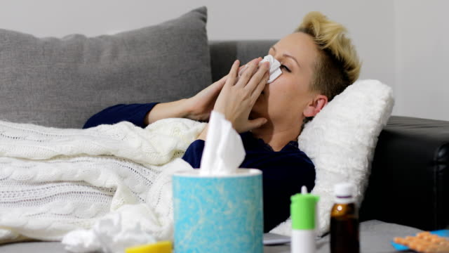 Sick young woman at home on the sofa with a cold, she is covering with a blanket and blowing her nose video