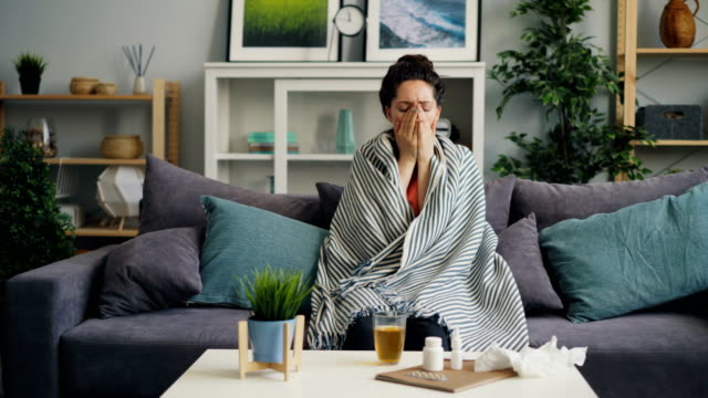 Sick young woman coughing drinking medicine sitting on couch at home Sick young woman coughing drinking medicine sitting on couch at home covered with warm blanket. Unhealthy people, medical problems and apartment concept. flu stock videos & royalty-free footage