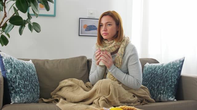 больная молодая женщина пьет чай с лимоном в домашних условиях - шарф стоковые видео и кадры b-roll