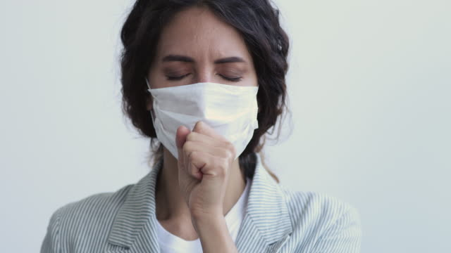 Sick young woman having pneumonia coughing wearing face mask Ill sick young woman having coronavirus pneumonia symptom short cough covers mouth wears medical face mask. Covid 19 virus infection spreading prevention, flu and cold treatment concept. Close up view short length stock videos & royalty-free footage