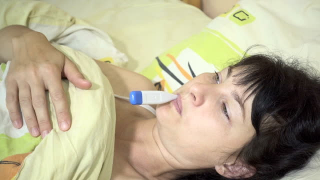 Sick Young womanl having her temperature taken with a digital thermometer.  Close-up. video