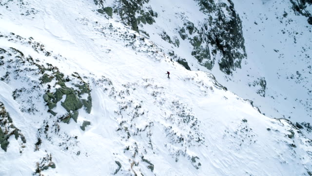 vídeos de stock e filmes b-roll de side aerial over winter snowy mountain with mountaineering skier people walking up climbing.snow covered mountains top and ice glacier.winter wild nature outdoor establisher.fullhd drone flight - alpes europeus