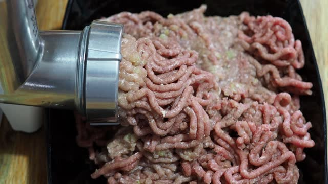 side and above view of grinding of minced meat and onion side and above view of grinding of minced meat and onion in electric meat grinder close up on wooden table at home kitchen ground beef stock videos & royalty-free footage
