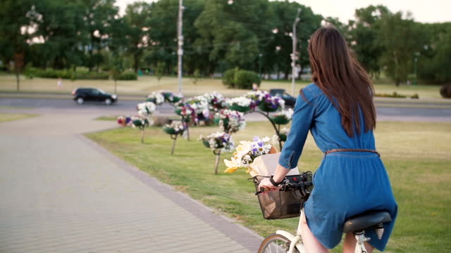 side and back view of a girl riding a bike near driven cars with flowers in a basket, slow mo, steadicam shot - cestino della bicicletta video stock e b–roll