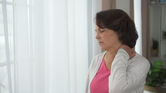 sidan av mogen kvinna massage halsen stående på fönsterbakgrund i hemmet bra - axel led bildbanksvideor och videomaterial från bakom kulisserna