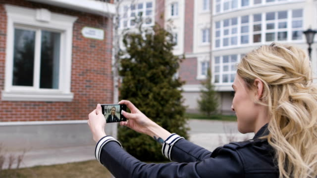side portrait of a beautiful blond girl using a smart phone to network, taking selfies pictures in a suburban home exterior, outdoors - preppy fashion stock videos and b-roll footage