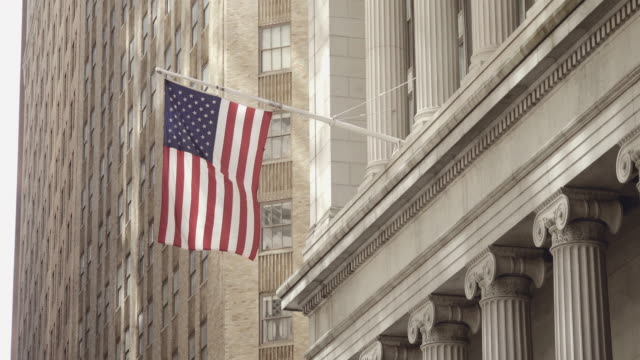Side shot of American flag waving in a calm breeze off a historical financial building on the Wall Street in Lower Manhattan, New York, United States Side shot of American flag waving in a calm breeze off a historical financial building on the Wall Street in Lower Manhattan, New York, United States in the afternoon wall street stock videos & royalty-free footage