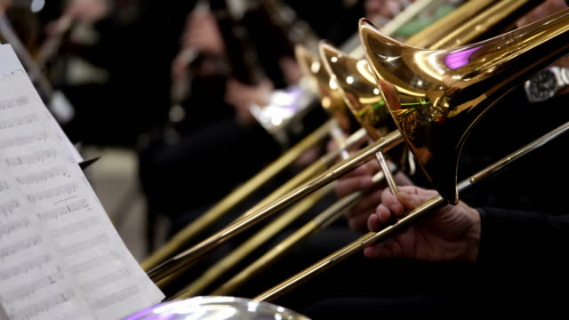 side shot of several musicians playing on their trombones and other musicians playing on their instruments - orchestra video stock e b–roll