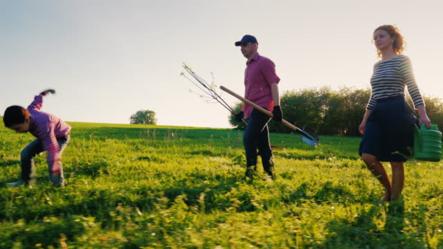 Side view: A family of farmers with a small son go together to plant a tree. Bear the apple tree seedlings, shovel and watering pad. Steadicam shot, side view video