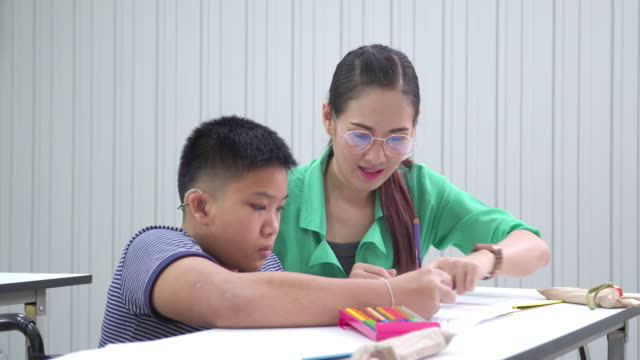 side view: a teenage boy with a disability in a wheelchair doing homework or assignment in the classroom with an Asian beautiful teacher in school. The boy is sitting at a table, writing, drawing art in paper with color pencils with assistance.