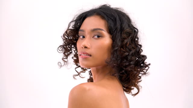 vue latérale: asiatique belle femme Tan touchant du menton à l'épaule sur fond blanc. Les gens avec beauté, soins de santé, concept d'émotion. - Vidéo