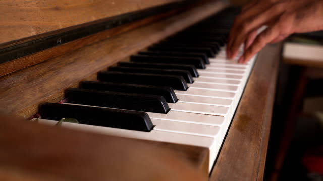 side view: Asian man's hand try to play Piano keyboard while standing