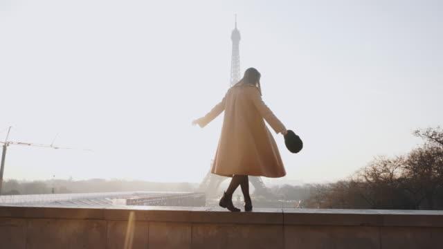 vidéos et rushes de vue de côté belle femme heureuse de touriste marchant, dansant au paysage romantique de tour eiffel de lever de soleil à paris au ralenti. - mode paris